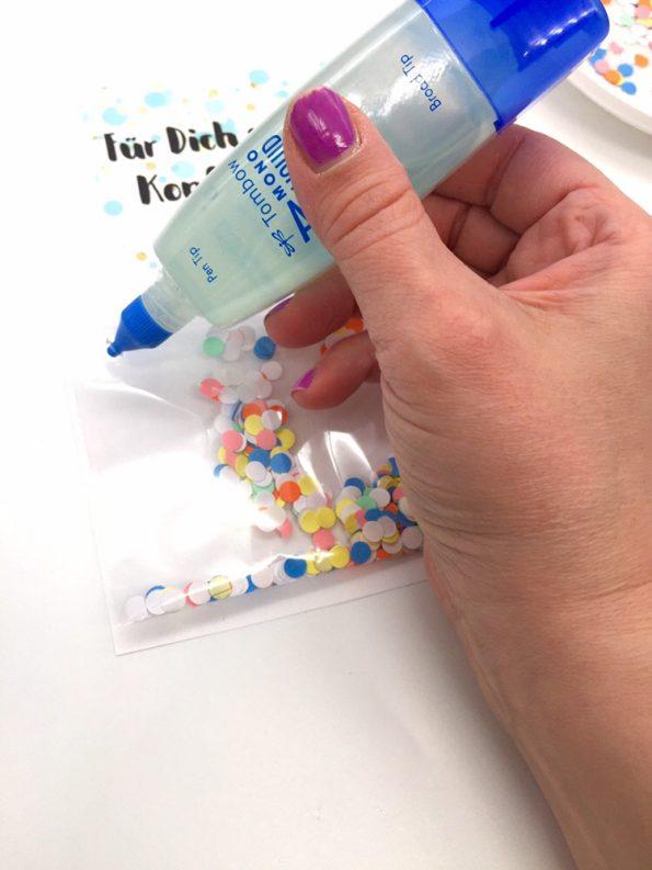 Süße Geschenkideen zum Geburtstag: Konfetti mit Kleber auf der Karte befestigen
