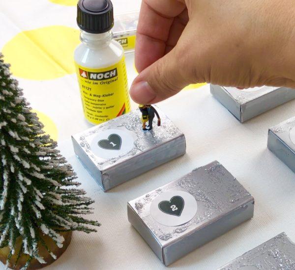 DIY Adventskalender: Die Modellfiguren werden auf den Streichholzschachteln platziert