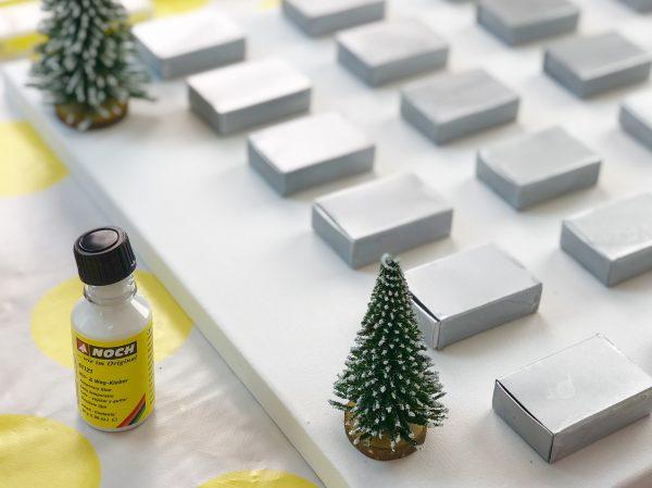 Deko Tannenbäume auf dem DIY Adventskalender festkleben